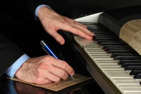 man hands playing piano and writes on parer for notes photo
