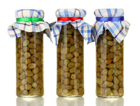Glass jars with tinned capers isolated on white photo