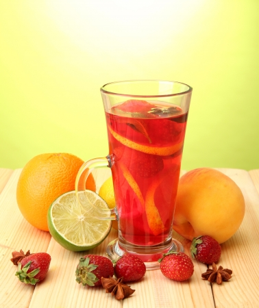 Refreshing sangria in glass with fruits, on wooden table, on green background photo