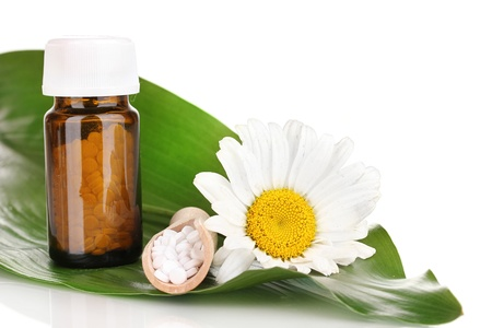 curative: homeopathic tablets and flower on green leaf isolated on white