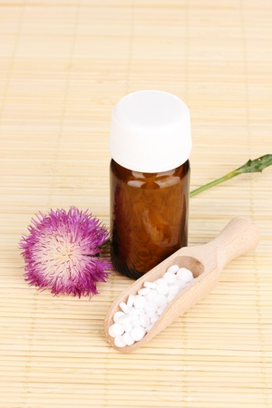 medicine bottle with tablets and flower on bamboo mat photo