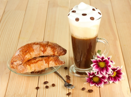 glass of fresh coffee cocktail and saucer with bagels on wooden background photo