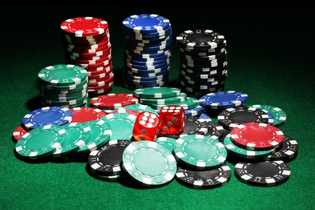 Dices and chips for poker on green table Stock Photo