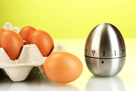 eggs in box and egg timer on green background Stock Photo - 15244102