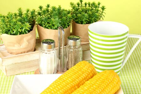 boiled corn and flowers on a green background photo