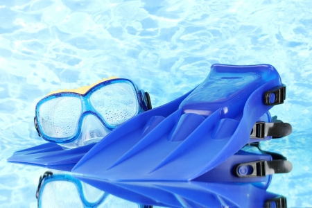 flippers: blue flippers and mask on blue sea background Stock Photo