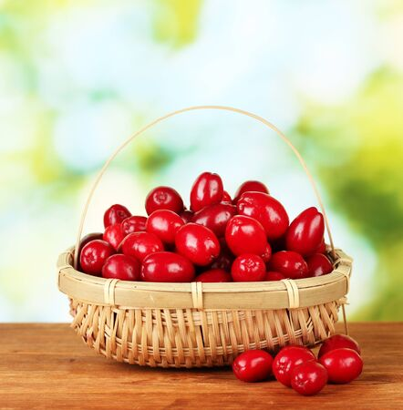 fresh cornel berries in wicker basket on green background close-up photo