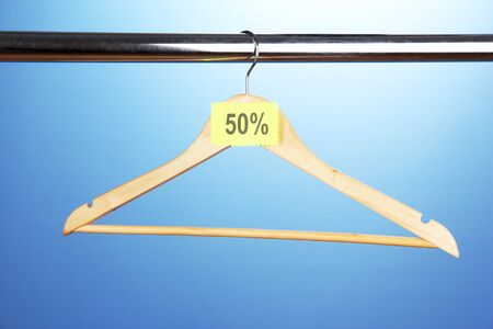 wooden clothes hanger as sale symbol on blue background  photo