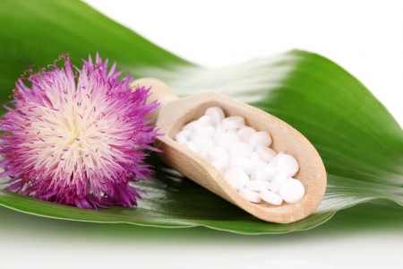nature cure: homeopathic tablets and flower on green leaf isolated on white
