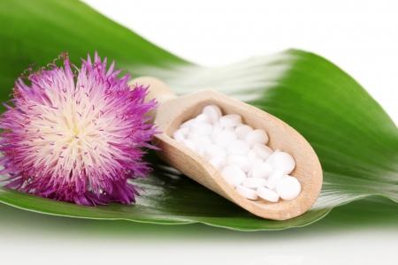 homeopatia: pastillas homeopáticas y la flor en la hoja verde aislado en blanco Foto de archivo