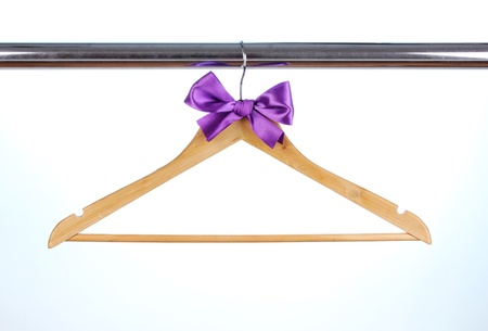 Beautiful purple bow hanging on wooden hanger on blue background photo