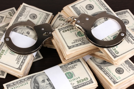 Handcuffs and packs of dollars on wooden table close-up Stock Photo - 15249455