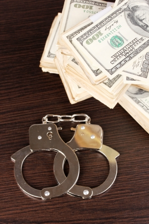 Handcuffs and packs of dollars on wooden table close-up Stock Photo - 15249454