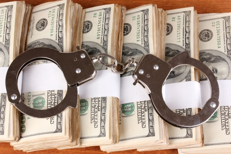 Handcuffs on the packs of dollars on wooden table close-up Stock Photo - 15249506