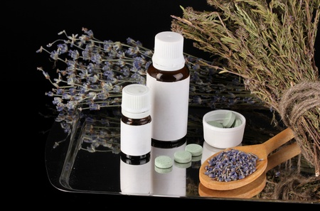 bottles of medicines and herbs on black background. concept of homeopathy photo