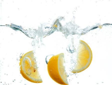 jus de citron: Tranches de citron dans l'eau isol� sur blanc