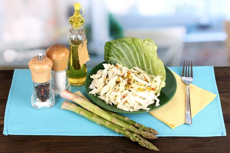 Plate with coleslaw and seasonings on wooden table on room background photo