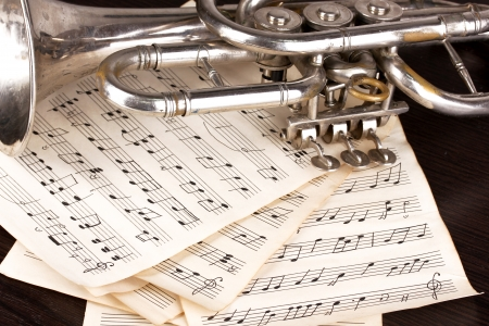 musical instrument parts: Musical notes and trumpet on wooden table Stock Photo