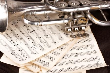 trompeta: Notas musicales y trompeta en la mesa de madera Foto de archivo