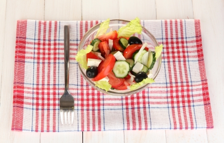 tasty Greek salad on white wooden background photo