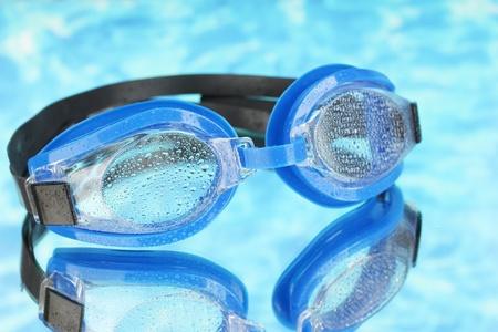 swim goggles: gafas de nataci�n azul con gotas en el fondo del mar azul