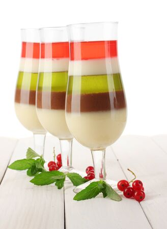 fruit jelly in glasses, redcurrants and mint on wooden table photo