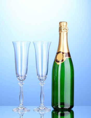 gold capped: Bottle of champagne and goblets on blue background