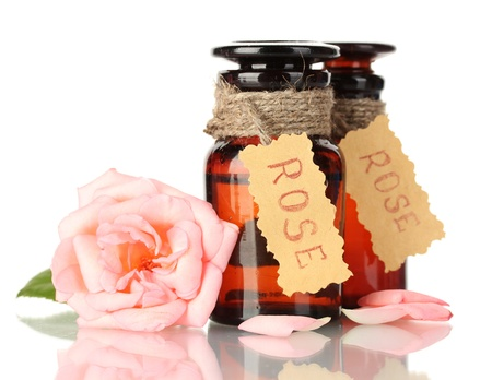essentials: bottles of oil and rose isolated on white