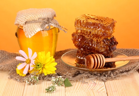 Jar of honey and honeycomb on wooden table on orange background photo