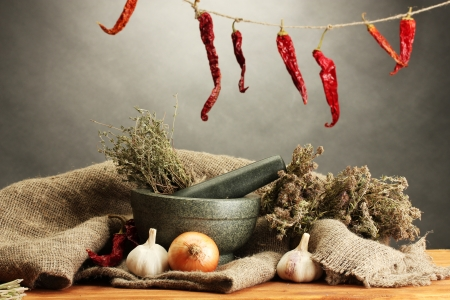 dried herbs in mortar and vegetables, on wooden table on grey\ background