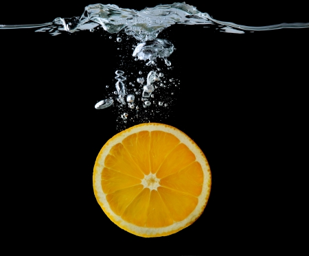Slice of orange in the water on black background photo