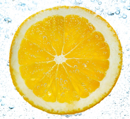 slice of orange in the water with bubbles, isolated on white photo