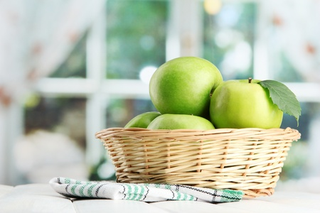 Ripe green apples with leaves in basket, on wooden table, on window background Stock Photo - 15369504
