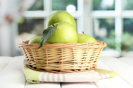 Ripe green apples with leaves in basket, on wooden table, on window background Stock Photo - 15369496