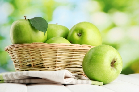 Ripe green apples with leaves in basket, on wooden table, on green background Stock Photo - 15369501