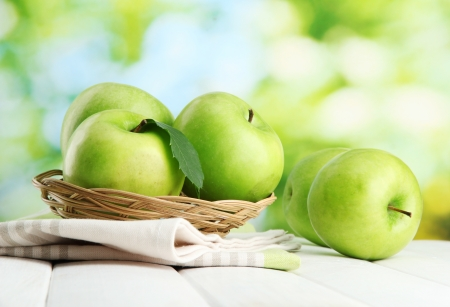 Ripe green apples with leaves in basket, on wooden table, on green background Stock Photo - 15410051