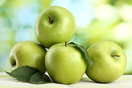 green apple: Ripe green apples with leaves, on table, on green background