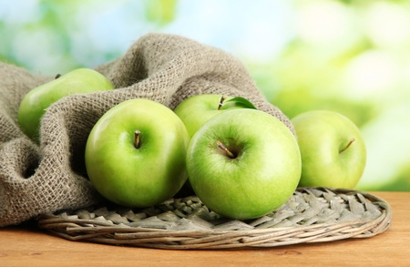 Ripe green apples on burlap, on wooden table, on green background photo