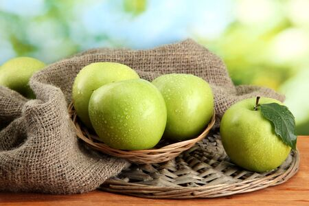 Ripe green apples in basket on burlap, on wooden table, on green background Stock Photo - 15410311