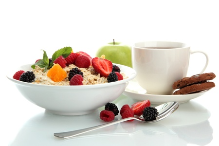 tasty oatmeal with berries and cup of tea, isolated on white photo