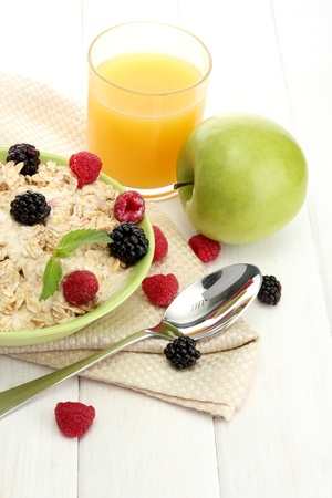 tasty oatmeal with berries and glass of juice, on white wooden table Stock Photo - 15369329