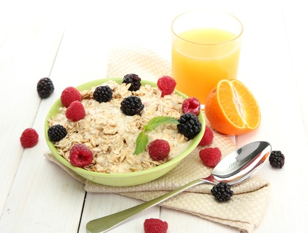 tasty oatmeal with berries and glass of juice, on white wooden table Stock Photo - 15368925