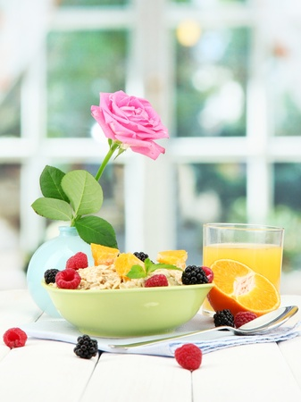 tasty oatmeal with berries and glass of juice on table, on window background Stock Photo - 15350517