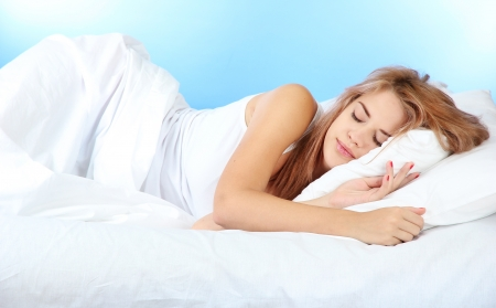 young beautiful woman sleeping on bed on blue background Stock Photo - 17129671