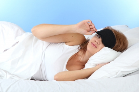 young beautiful woman sleeping in bed with eye mask on blue background photo