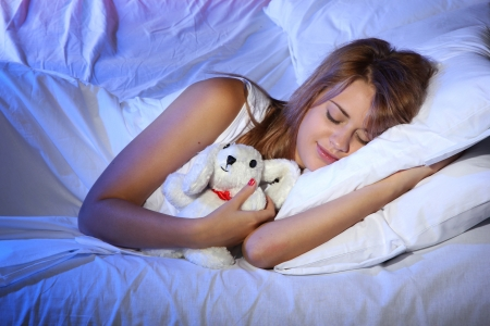 young beautiful woman with toy rabbit sleeping on bed in bedroom photo