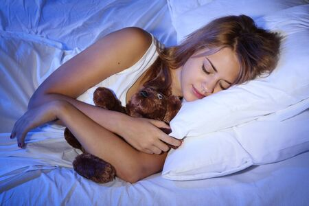 young beautiful woman with toy bear sleeping on bed in bedroom Stock Photo - 17187340