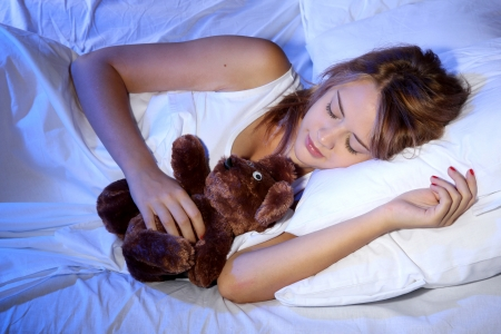 young beautiful woman with toy bear sleeping on bed in bedroom Stock Photo - 17187342