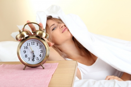 young beautiful woman lying on bed with alarm clock in bedroom photo