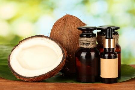 aceite de coco: aceite de coco en botellas de cocos sobre fondo verde